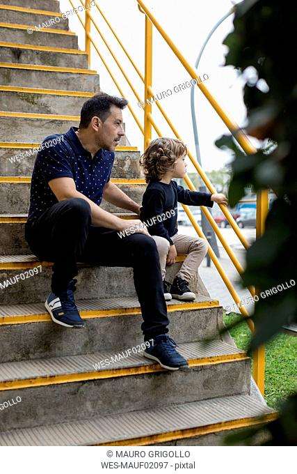 Father and son sitting on stairs in the city