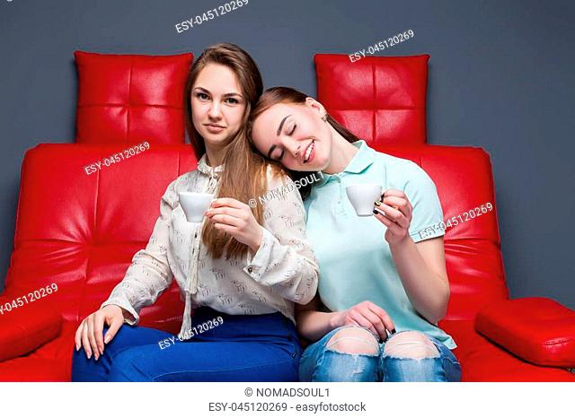 Two girls with cups of coffee sitting together on red leather couch. Women gossip