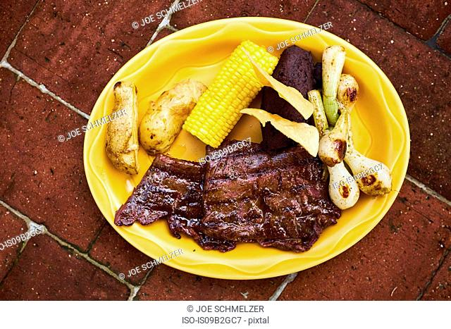 Overhead view of plate with meat and corn on the cob, Antigua, Guatemala