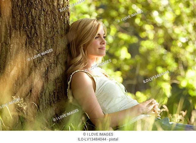 A young woman leaning against a tree, resting