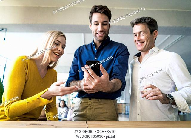Happy business team looking at cell phone together in loft office