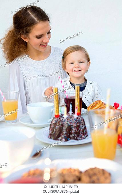 Teenage girl and toddler at patio table for birthday party