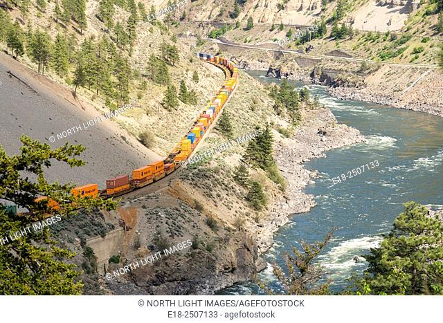 Canada, BC, Lytton. Train cars with shipping containers snaking through a steep valley in the Thompson River Canyon