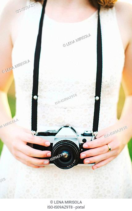Cropped view of woman holding camera
