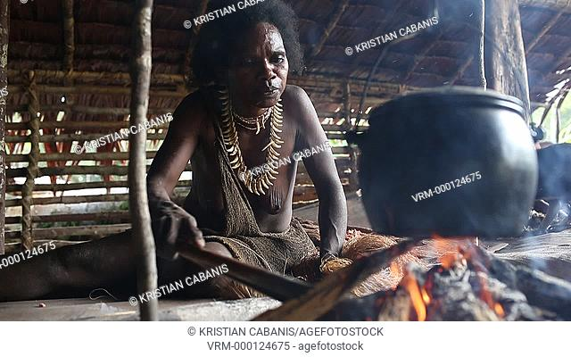 Woman from the Kombai tribe sitting at the fire place, Papua, Indonesia, Southeast Asia