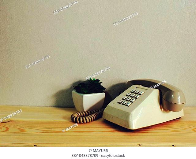 retro telephone on wood table wall background