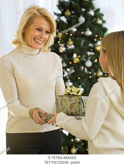 Grandmother and granddaughter holding Christmas gifts