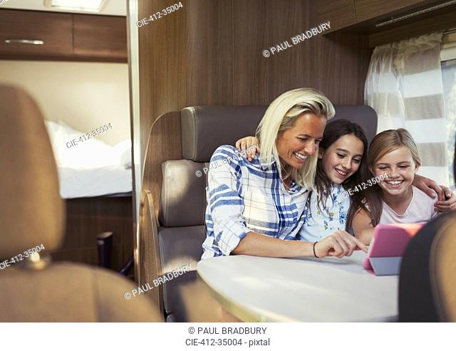 Smiling mother and daughters using digital tablet inside motor home