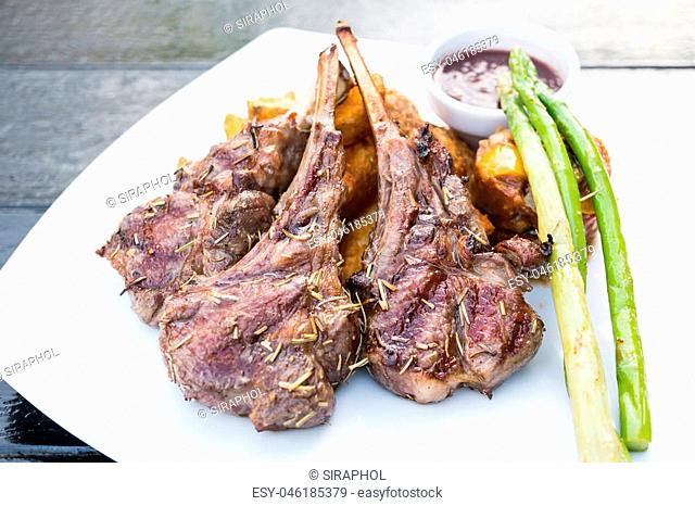 Grilled lamb chop steak with french fries in white plate