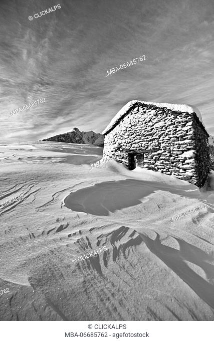 Black and white photograph depicting a cabin of Olano Alp whitewashed by a snow storm. Rasura. Valgerola. Alps Orobie. Valtellina. Lombardy. Italy