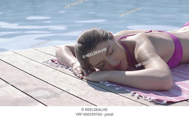 Attractive woman sunbathing by pool