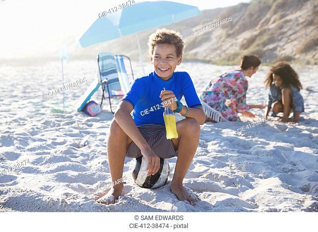 Smiling boy drinking juice on sunny summer beach