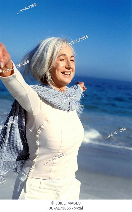 Portrait of a middle aged woman spreading her arms at the beach