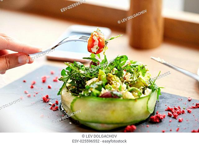 food, culinary, haute cuisine and people concept - woman eating cottage cheese salad with vegetables and dried raspberries at restaurant or cafe