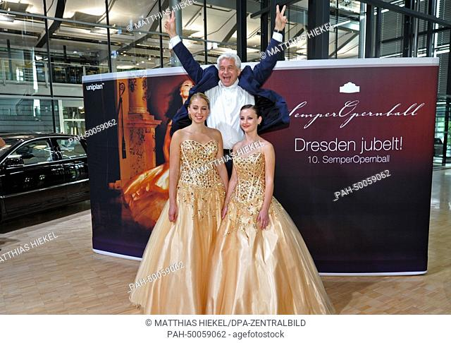 Chairman and Artistic Director of the SemperOperaball Hans-Joachim Frey jumps up behind models Cecile (L)and Leontine who wear the debutant's dress for the...