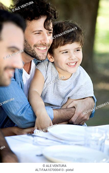 Father and young son with friends at outdoor meal
