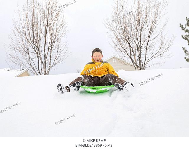 Smiling boy sliding on toboggan on hill in winter