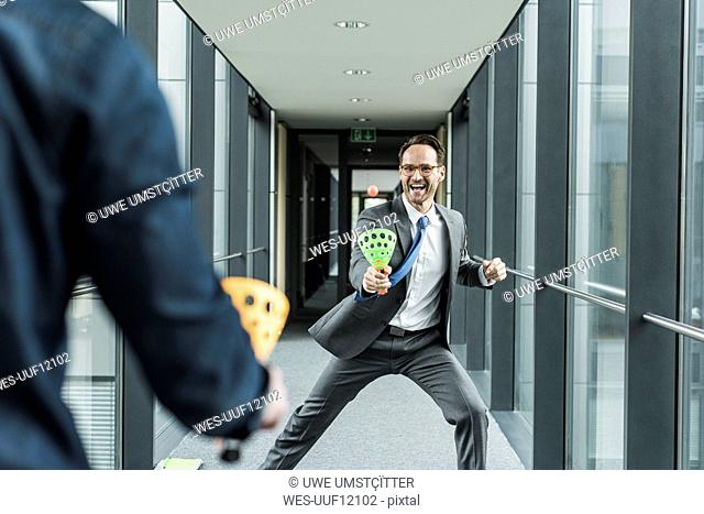 Businessman playing with colleague on the corridor