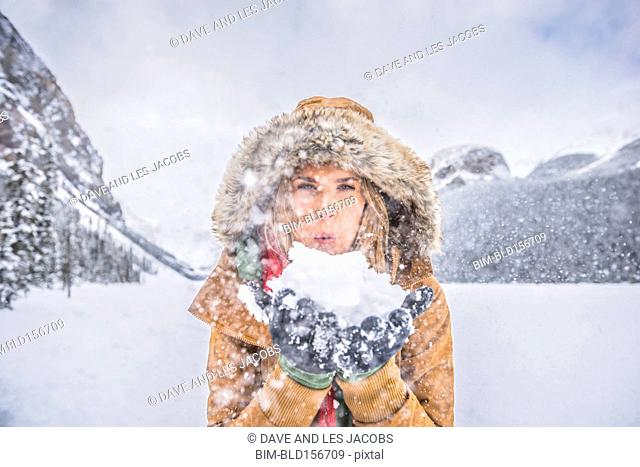 Caucasian woman blowing snow near mountains, Lake Louise, Alberta, Canada