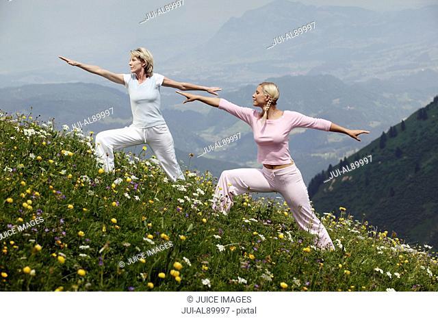 Two women practicing yoga, Kleinwalsertal, Allgau, Germany