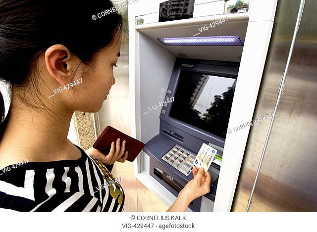 Young chinese at a bancomat. - Xiamen, Fujian, China, 04/05/2007