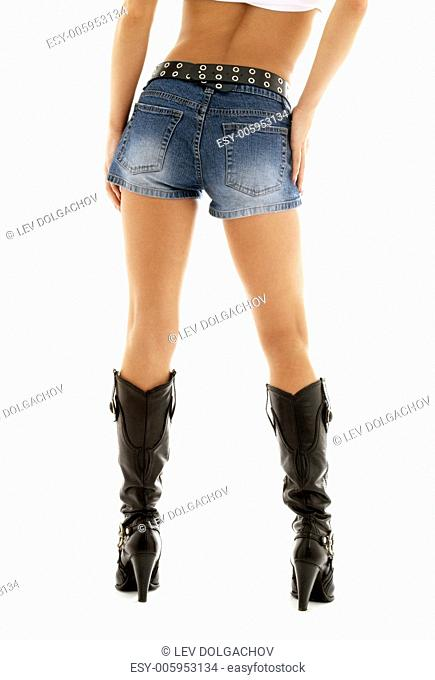 long legs in cowboy boots and denim shorts over white