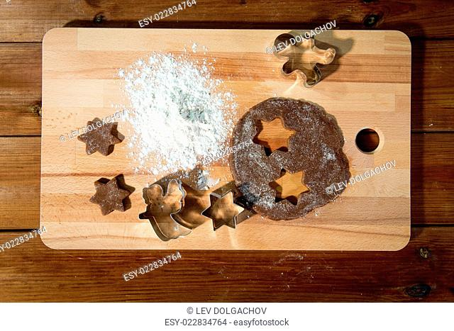 baking, cooking, christmas and food concept - close up of ginger dough, molds and flour on wooden cutting board from top