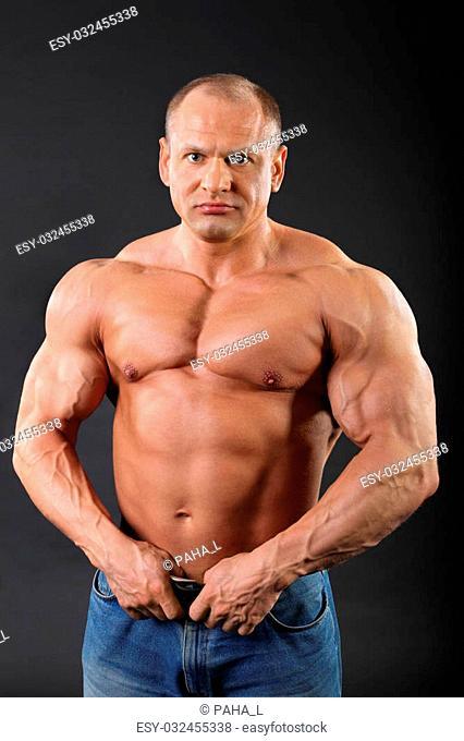 Sunburnt bodybuilder wearing in jeans keeps his belt inside black studio