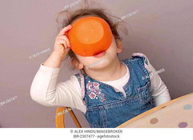 Three year old girl finishing snack from a bowl