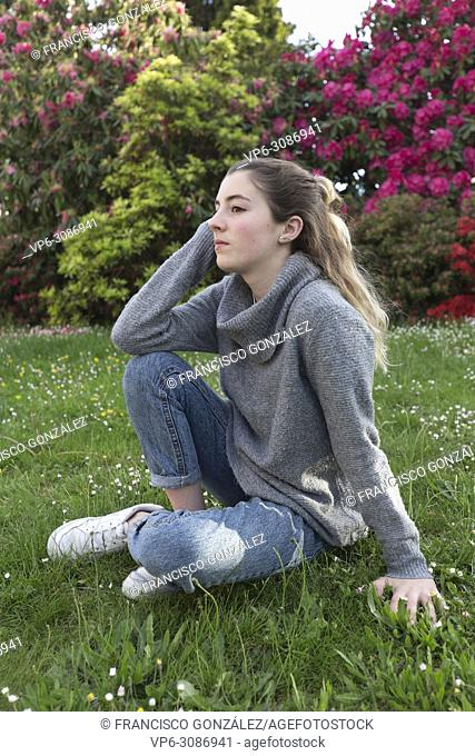 16 year old teenager sitting in a park with grass and flowers, taken in Limoges, France