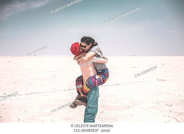 Couple on salt flats, hugging, Jujuy, Salinas Grandes, Argentina