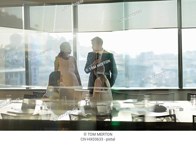 Business people talking in sunny, urban conference room meeting