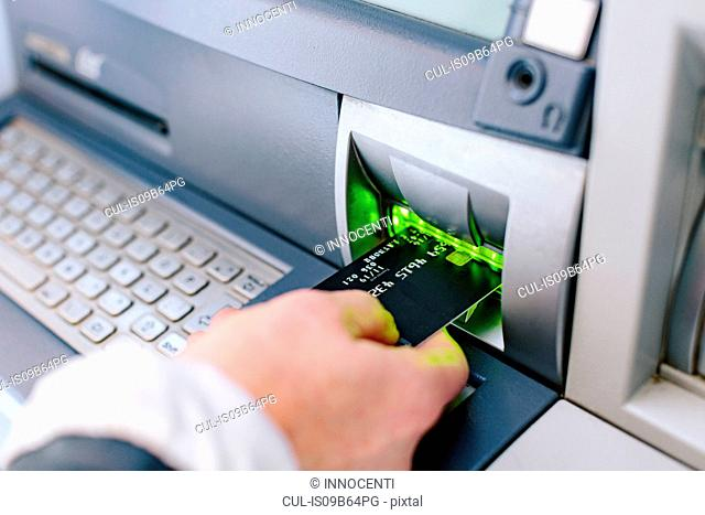 Close up of woman's hand inserting credit card into cash machine