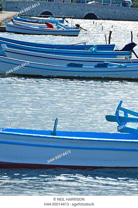 Blue Fishing boats moored up against the shore on a calm sea