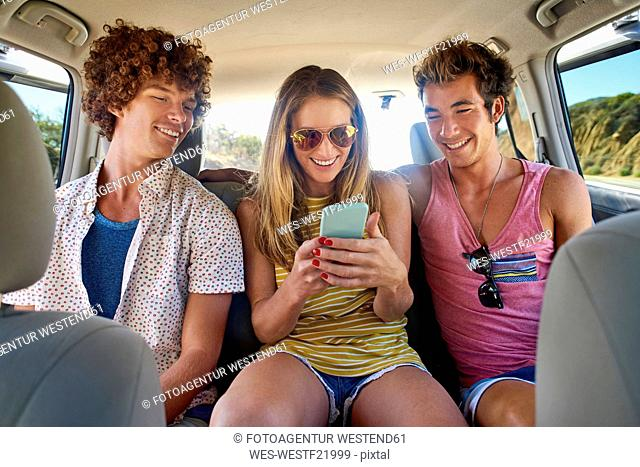 Happy friends checking cell phone in a car