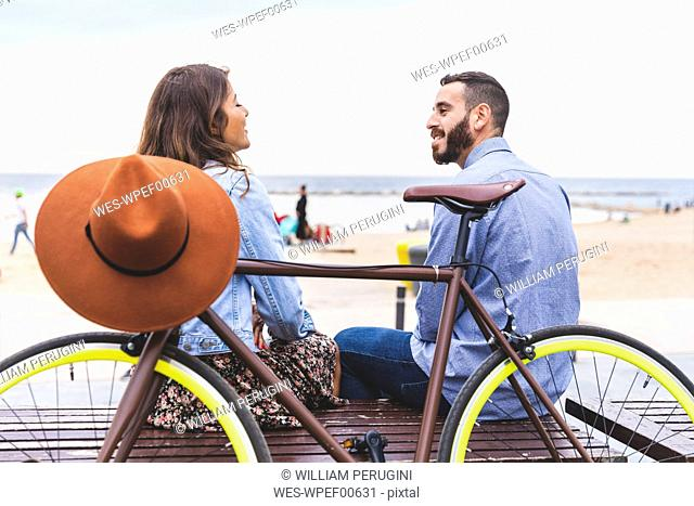 Spain, Barcelona, couple with bicycle sitting at the seaside