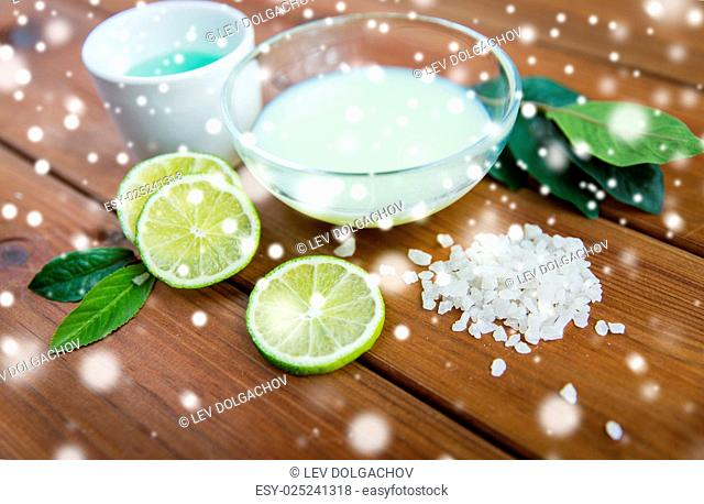 beauty, spa, bodycare and natural cosmetics concept - bowls with citrus body lotion, cream and sea salt on wooden table over snow