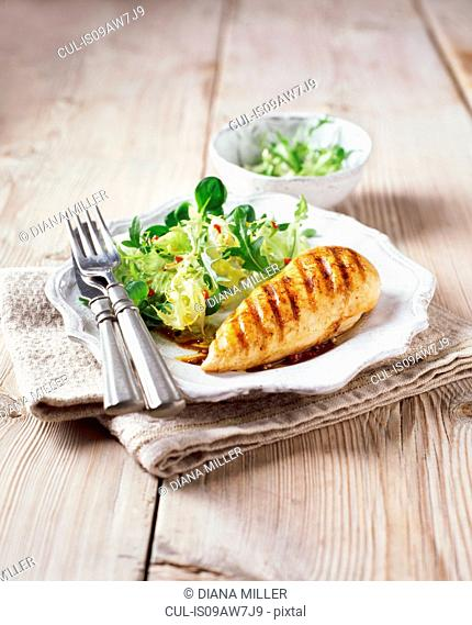 Char grilled chicken breast with leafy salad and dressing