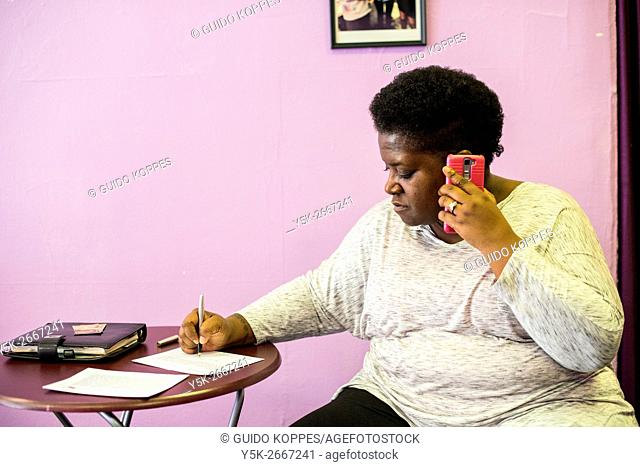 Newark, New Jersey, USA. LGBTQ Community Center volunteer Tyett making a phone call with one of their visitors