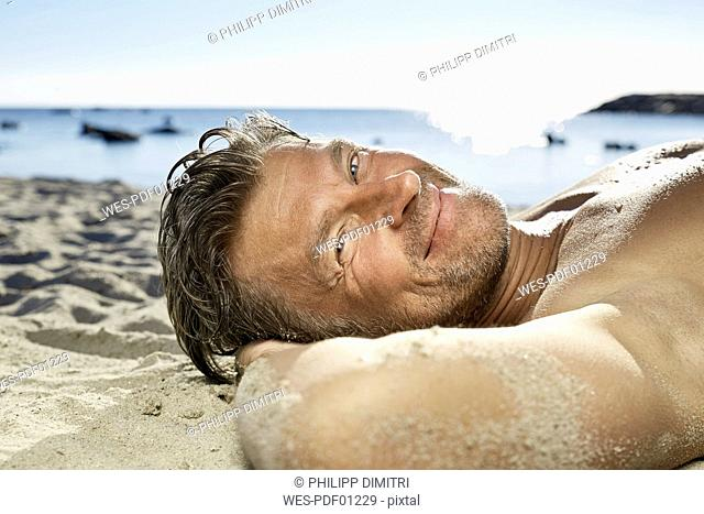 Portrait of man relaxing on sandy beach