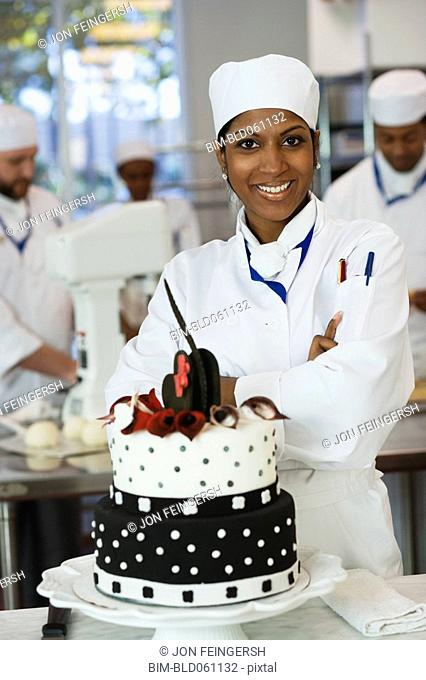 Mixed Race female pastry chef next to cake