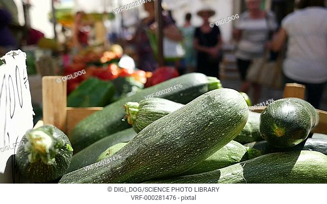 Fresh courgettes for sale in a market in a wooden basket