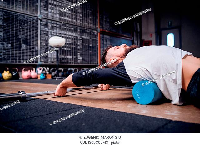 Young man massaging lower back with foam roller in gym