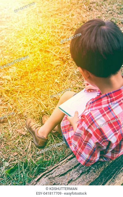 Back view. Child use pen to writing on book in park. Outdoors in the day time with bright sunlight. Children read and study, education concept