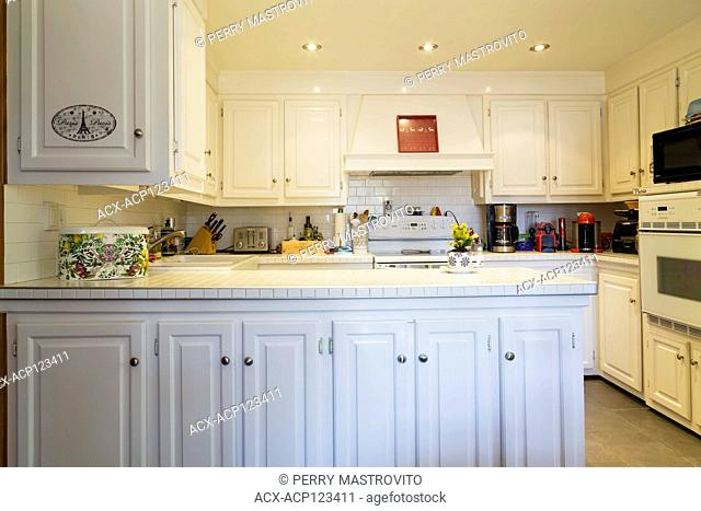 Country style kitchen with white cabinets and ceramic tile countertop inside old 1850 Canadiana cottage style house, Montreal, Quebec, Canada