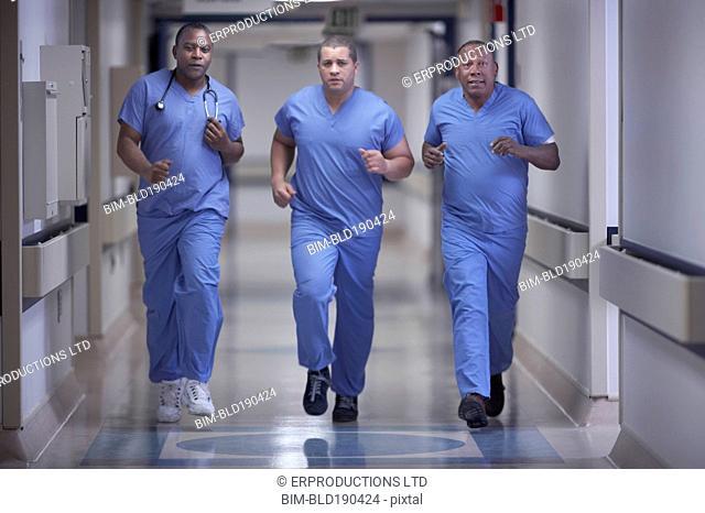 Multi-ethnic medical professionals running in hallway
