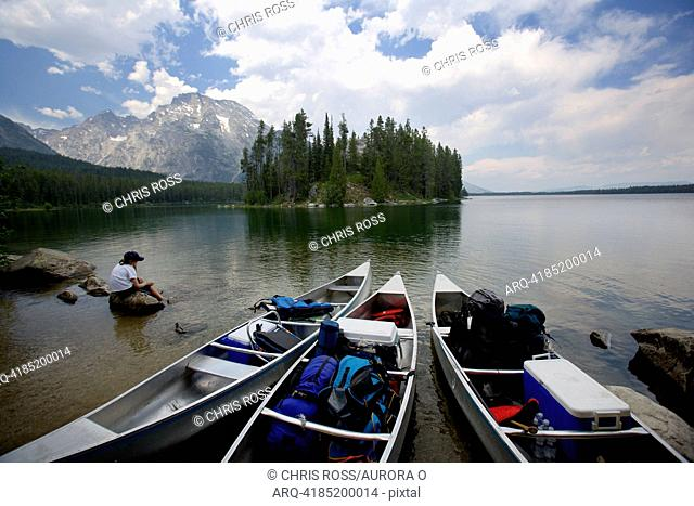 A boy sits contemplating on a lake rock while looking at the Grand Tetons