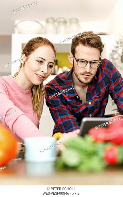 Young couple using tablet cooking together in kitchen