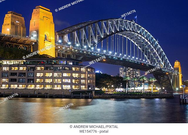 Sydney Harbour Bridge with Hyatt Park Hotel at dusk. Sydney, NSW, Australa