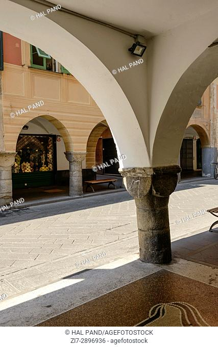 stone pillar at old medieval covered walkway, shot at Mediterranean little town of Chiavari, Genova, Liguria, Italy